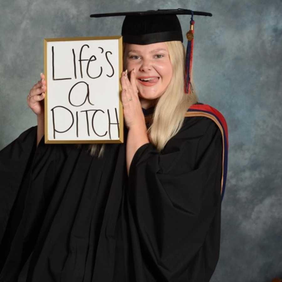 graduating high schooler holds up sign