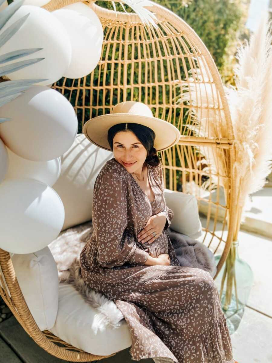 Woman expecting her fourth child takes pregnancy announcement photos in an animal-patterned dress while sitting in her backyard