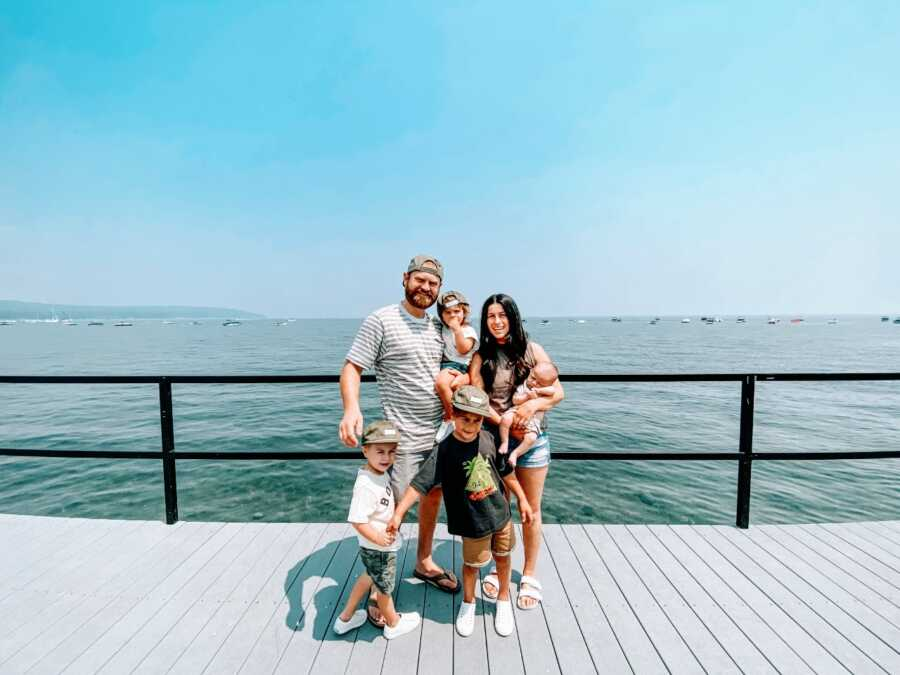 Couple take a family photo with their four sons under five while out on a walk on a boardwalk with the water behind them