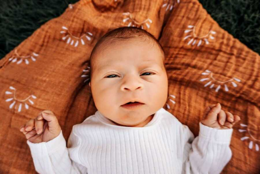 Mom takes a photo of her newborn son named Sonny laying on a blanket with suns on it while wearing a white sweater