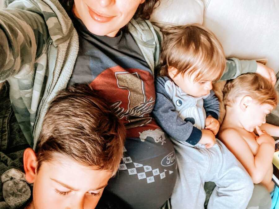 Heavily pregnant mom cuddles with her three sons on the couch