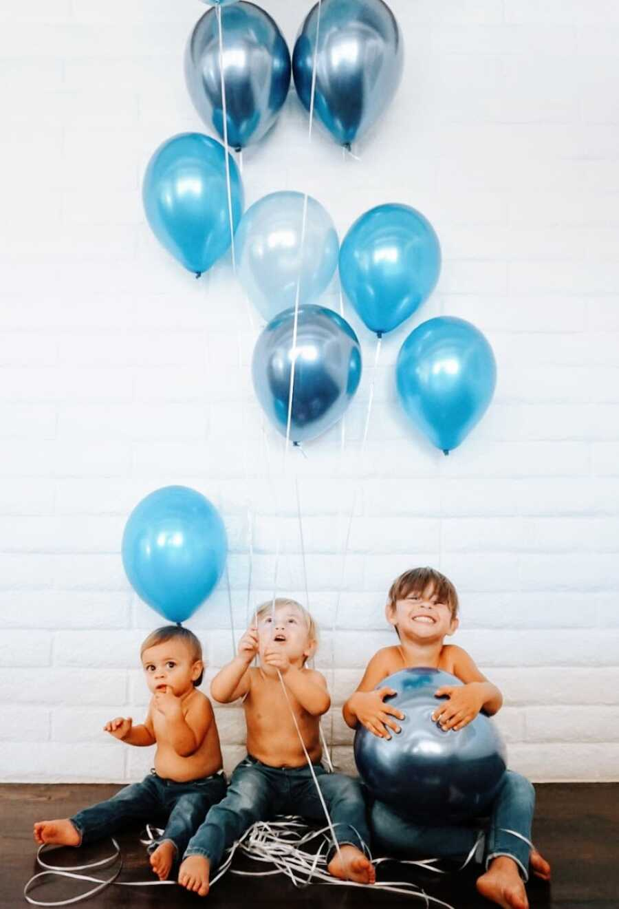 Couple expecting their fourth baby announce the gender by taking a photo of their three sons holding blue balloons