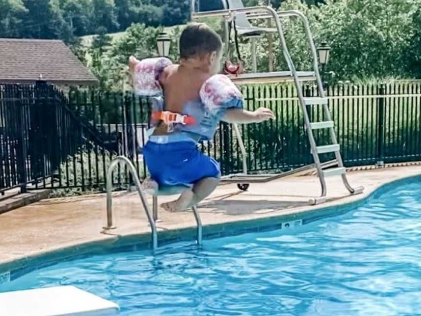 Mom snaps photo of adopted son jumping off the diving board at the local community pool