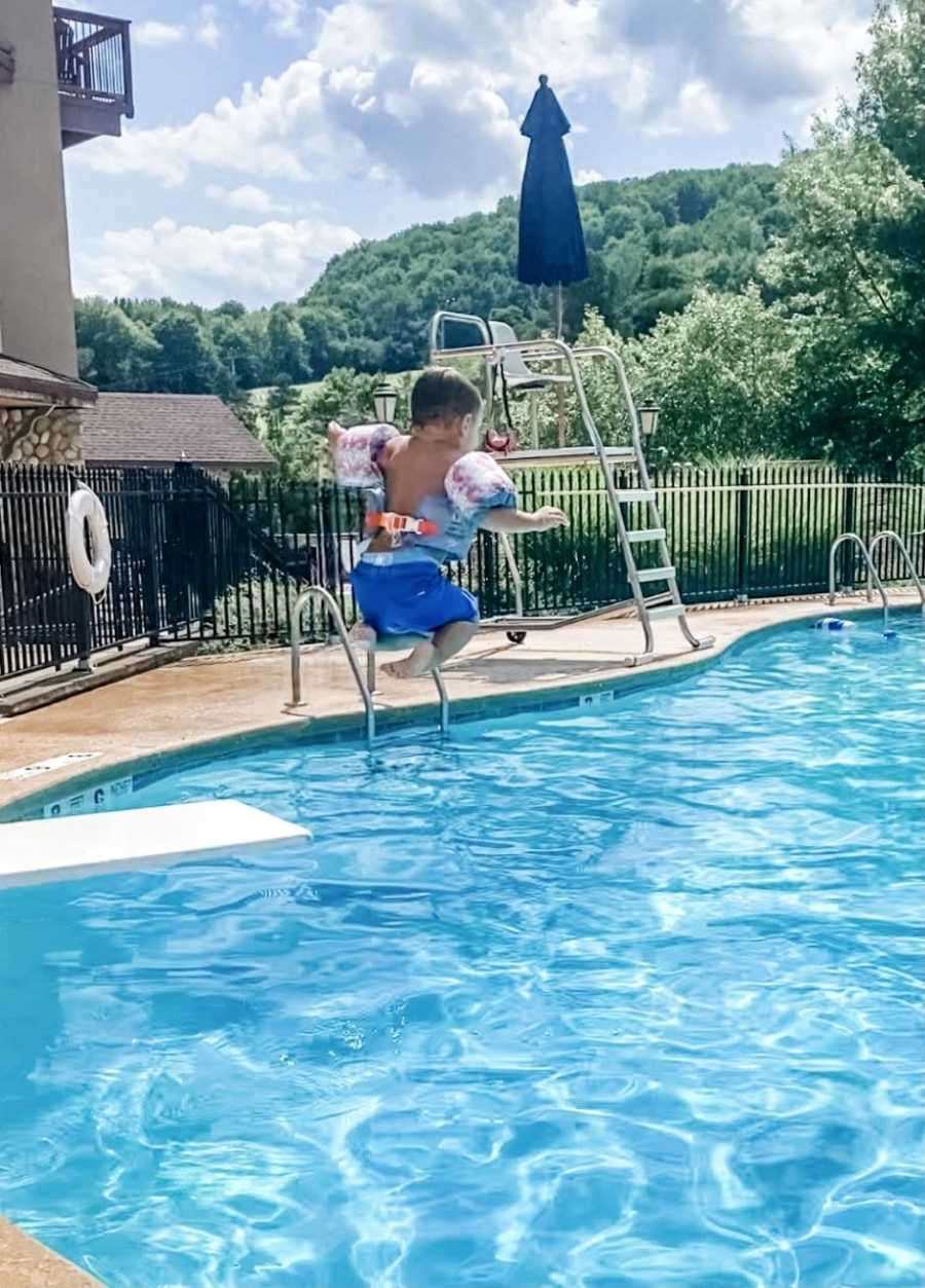 Little boy jumps off diving board during a summer pool day wearing floaties