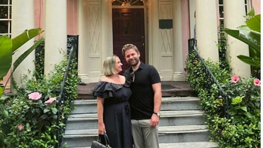 Couple in black outfits standing outside house