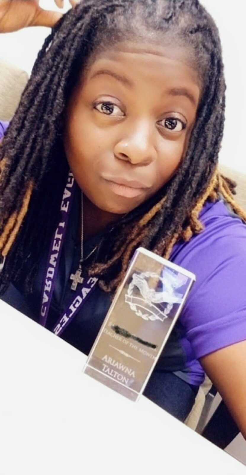 """Teacher of 11 years takes a photo with her """"Teacher of the month"""" award"""
