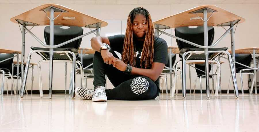 Young woman leaving her teaching profession after 11 years takes a photo sitting on the floor with classroom seats behind her
