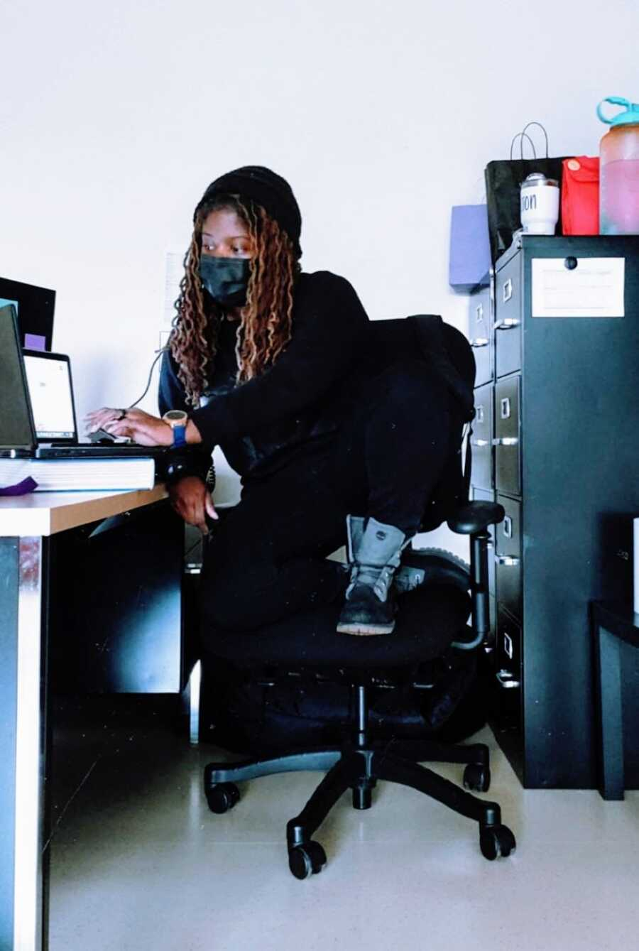 Teacher trying to teach in-person wears an all-black outfit with a black mask
