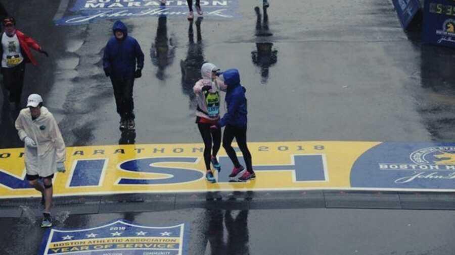 Two people in rain slickers hugging at the Boston Marathon finish line
