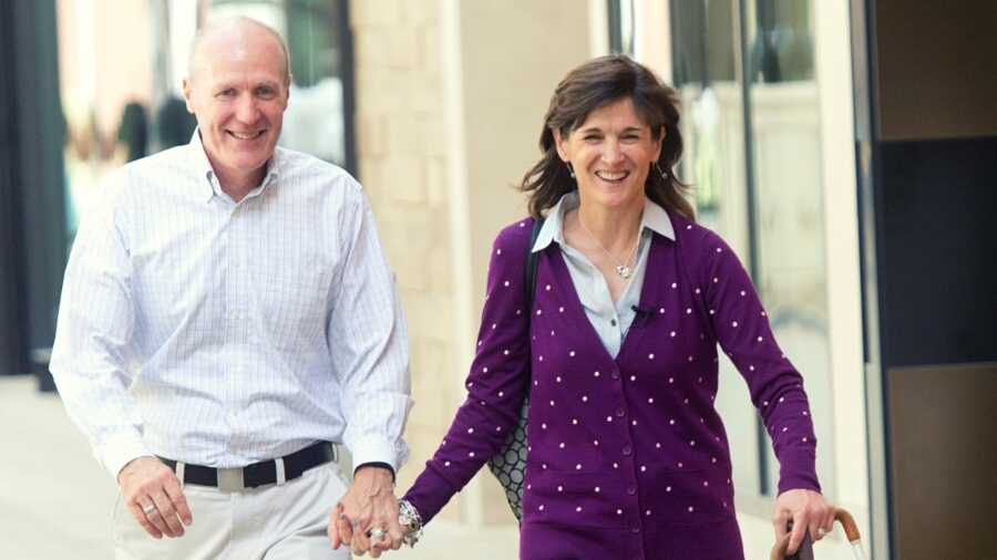 Wife in purple sweater holding hands with husband in white button down