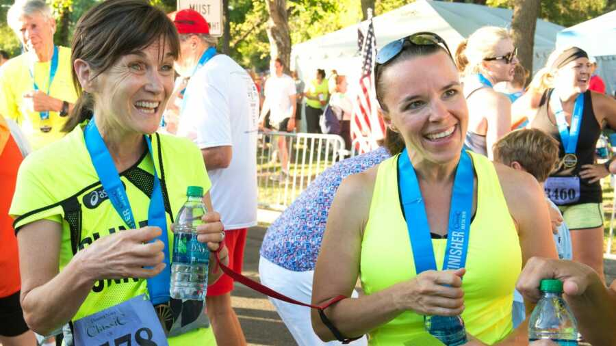 Two women in neon yellow shirts holding water bottles at start line of marathon