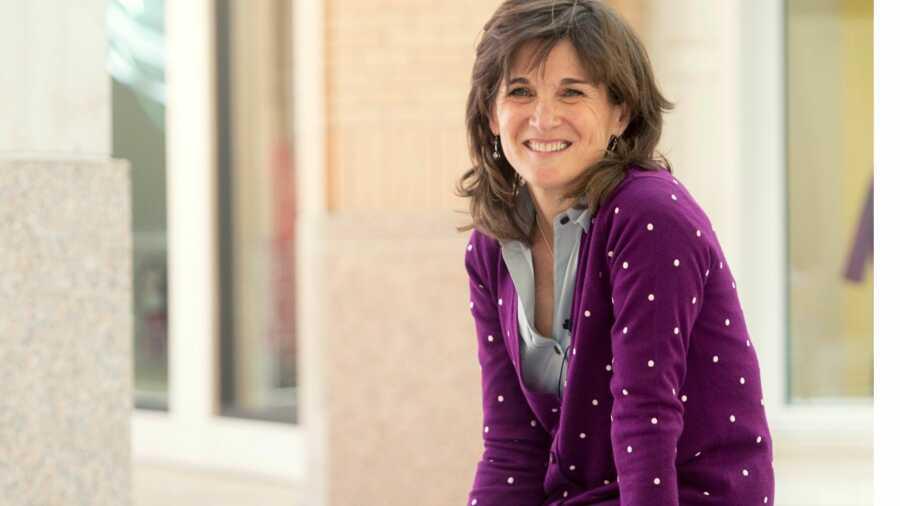 Woman in purple cardigan smiling