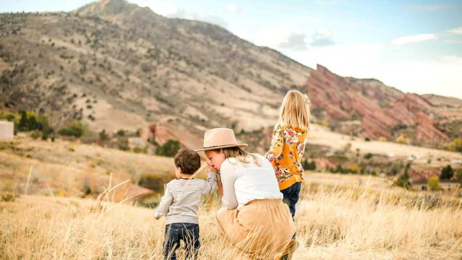 mom and two children in front of mountains