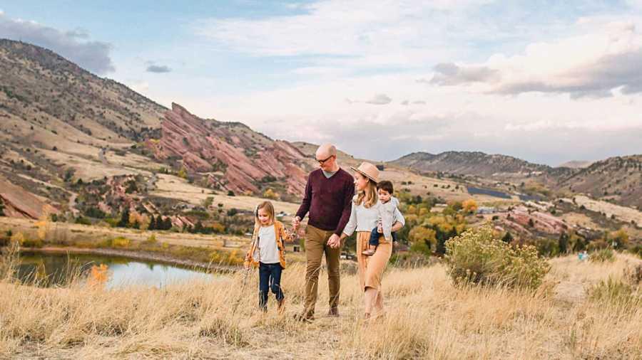 family of four walking through mountains