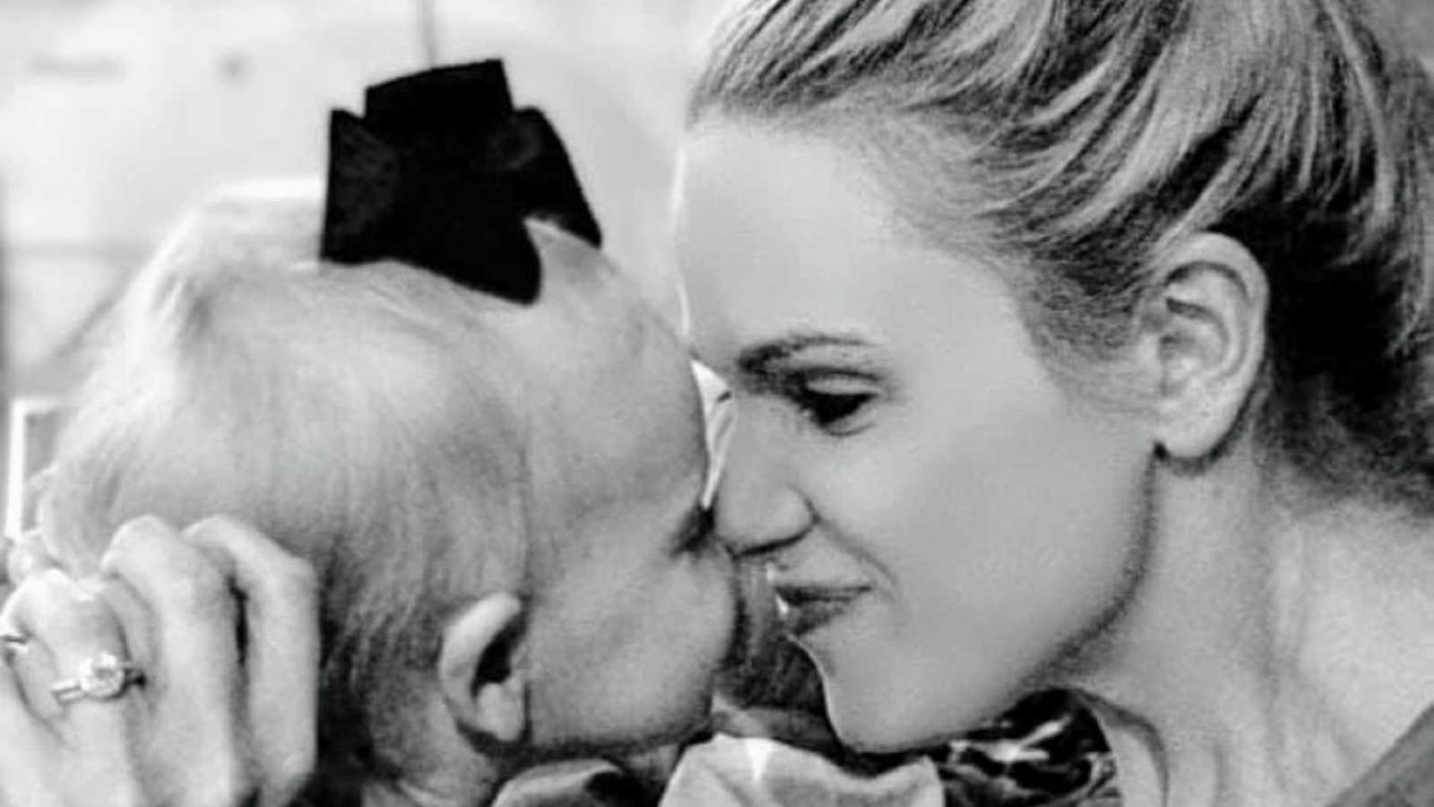 Girl mom and toddler daughter rubs noses together and smile during playtime