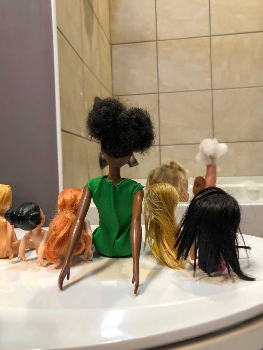 Mom teaching daughter lesson on diversity and kindness snaps photo of daughter playing in tub with Barbies