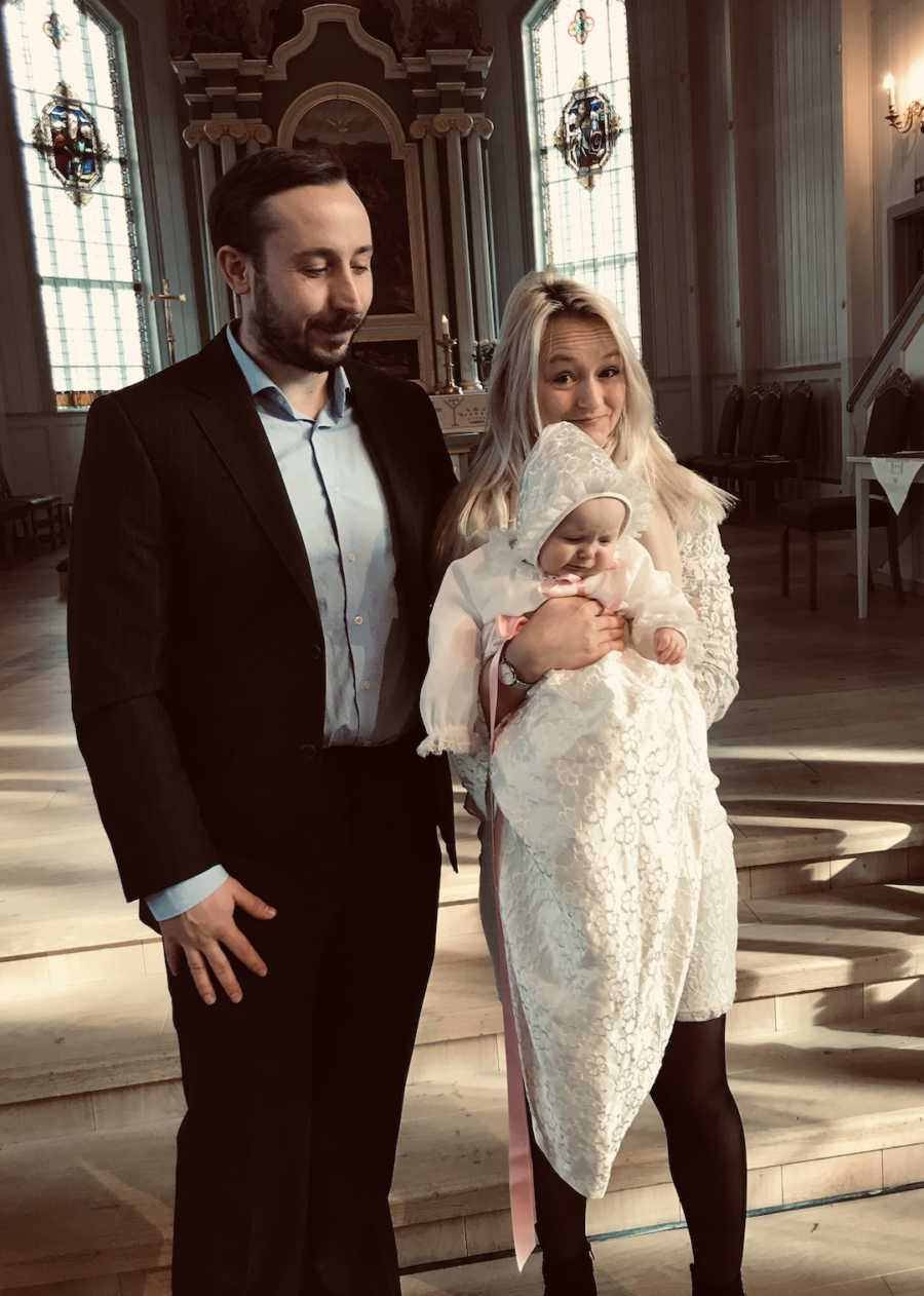 mom holding her baby standing next to her husband