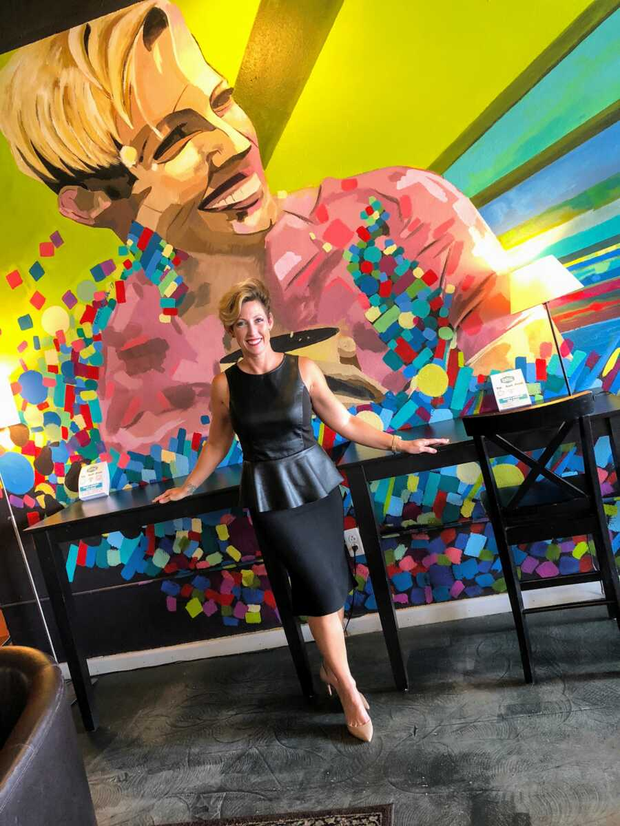 Woman suffering from an autoimmune disease, Alopecia, takes a photo in a black dress with a mural of herself in the background