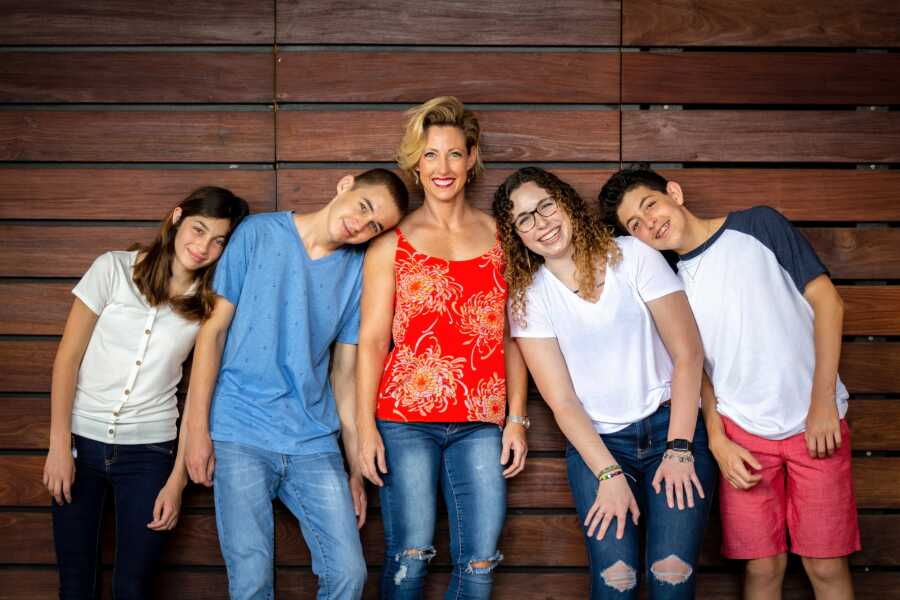 Single mom of 4 poses for a family photo with her children all resting their heads on each other's schoulders