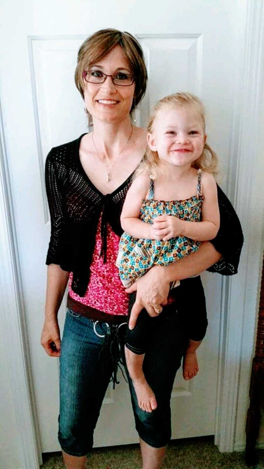 Mom of 4 holds her young daughter as they both grin at the camera