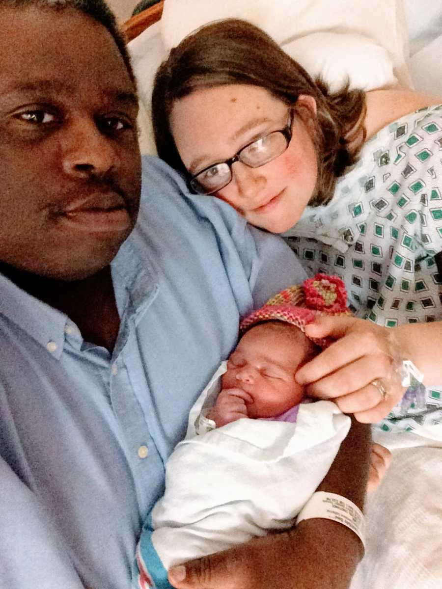 Couple who have experienced multiple miscarriages hold their newborn daughter together after the mom gave birth