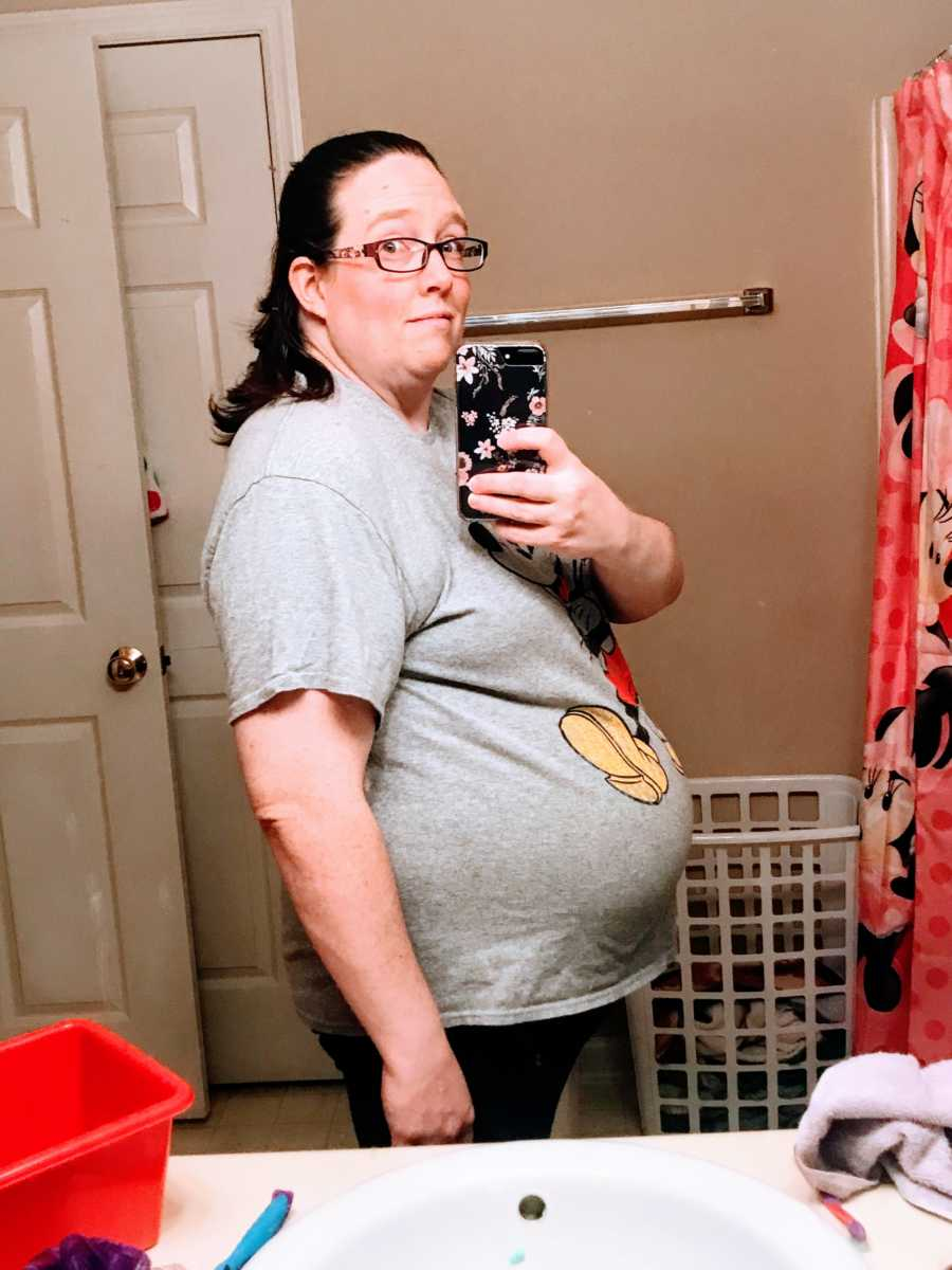 Woman pregnant with twins takes a photo of her growing belly bump in the bathroom mirror with a Mickey Mouse shirt on