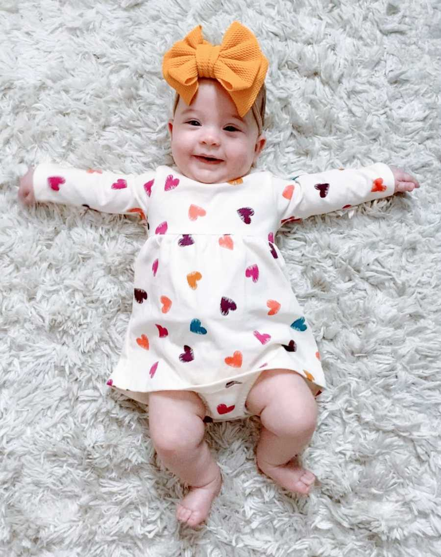 Young mom snaps photo of her miracle rainbow daughter smiling while laying on the floor in a heart onesie and a yellow bow on her head