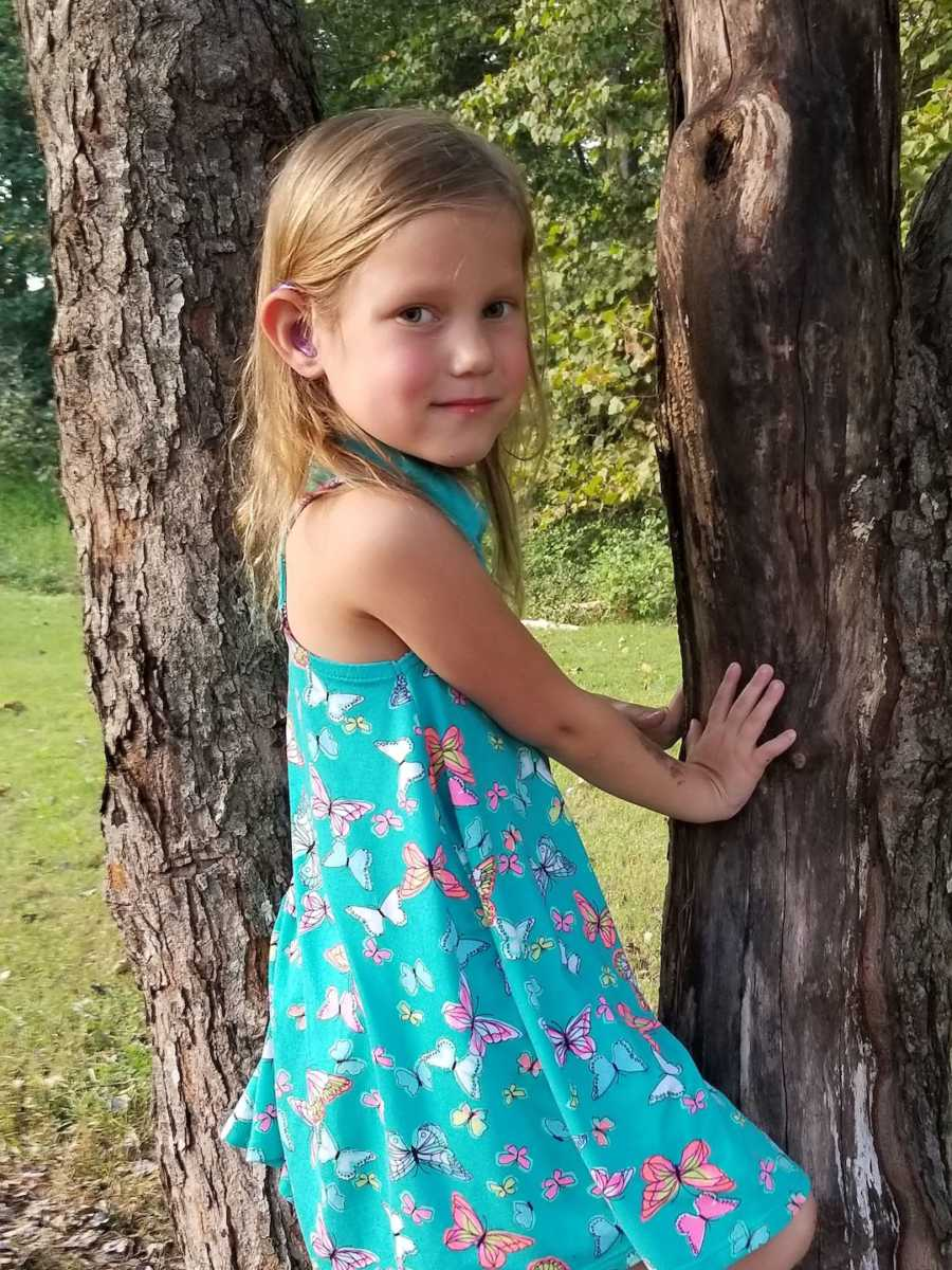young girl holding onto a tree with hearing aids