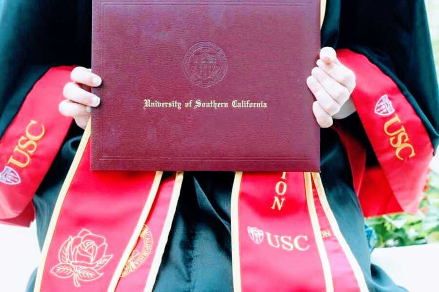 College student graduating from University of Southern California magna cum laude takes a photo with her diploma in her official robes and graduation gown