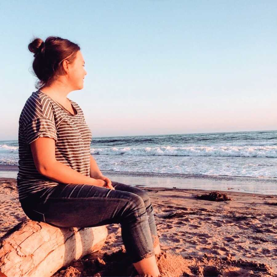Young independent woman takes a photo watching the sunset on the beach while sitting on a log