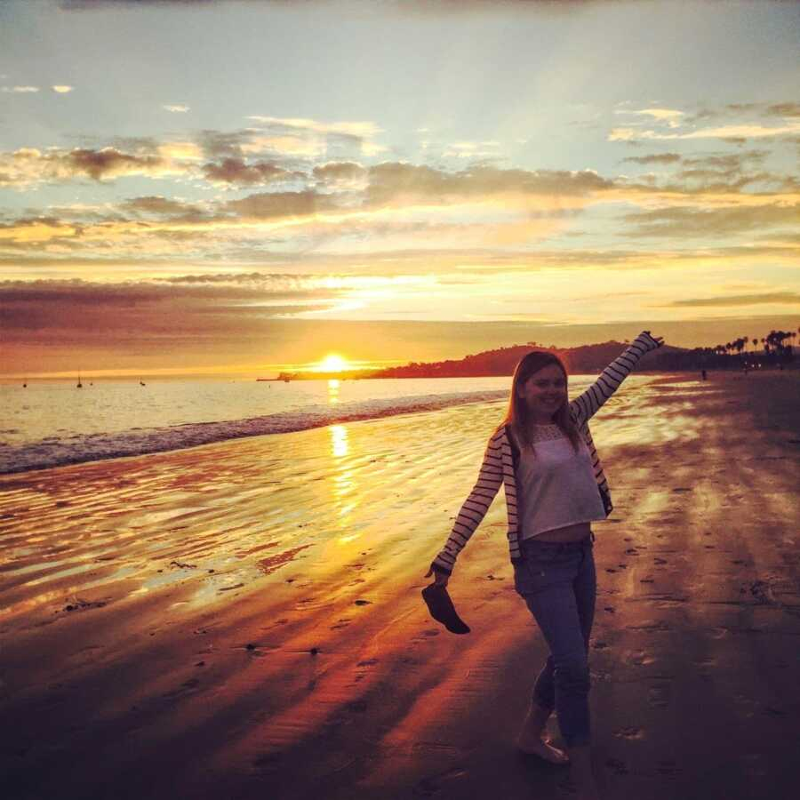 Young college student studying abroad in Europe takes a photo on a European beach during the sunset
