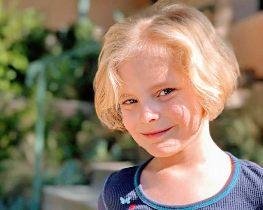 Little girl with a blonde bob smiles for a photo in a blue shirt with butterflies