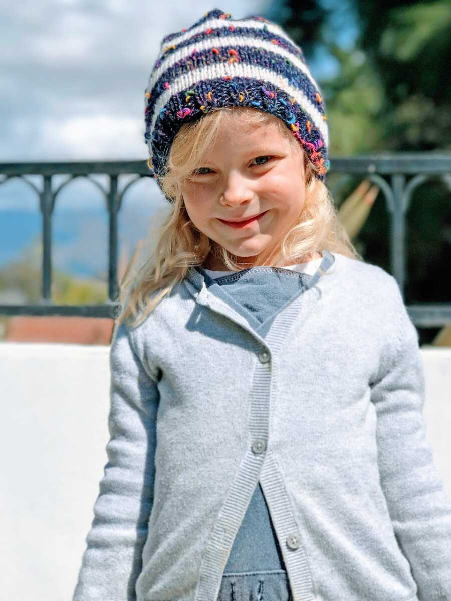 Little girl smiles big for a photo in a gray cardigan and speckled beanie