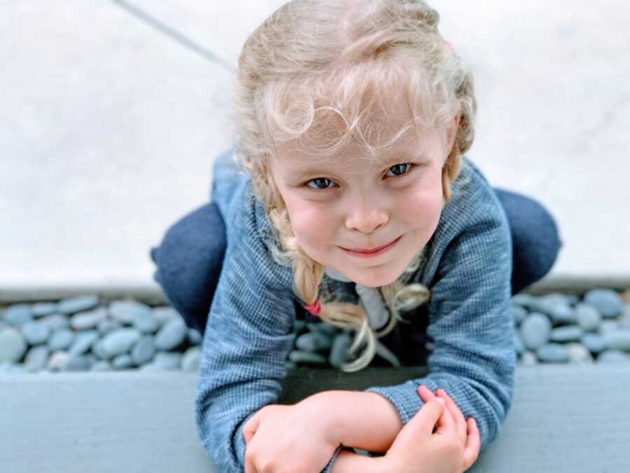 Little girl with blonde hair and blue eyes squats over a pile of rocks