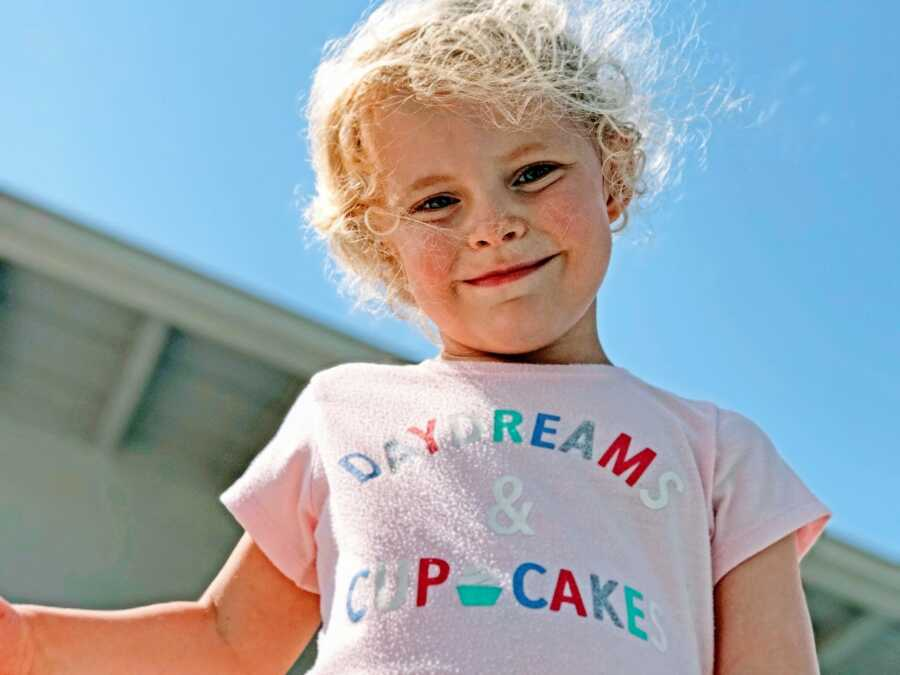 """Little girl smiles down at a camera while wearing a pink shirt that says """"Daydreams & Cupcakes"""""""