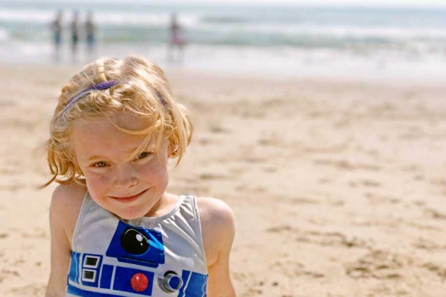 Young girl with a blonde bob smiles on the beach in an R2-D2 one-piece bathing suit