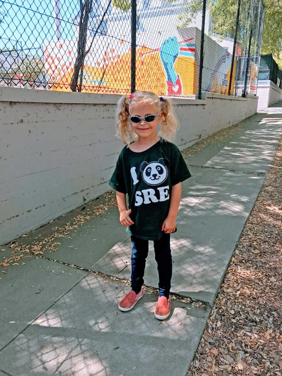 Little girl smiles for a photo while on a walk wearing a panda shirt and sunglasses