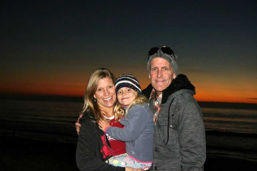 Parents smile big for a photo with their only daughter during the sunset on a beach while bundled up in winter clothes