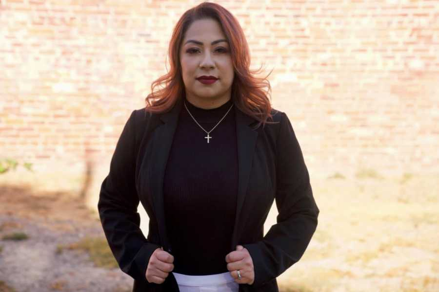Woman who started her own nonprofit after surviving human trafficking stands tall and strong with a cross necklace on