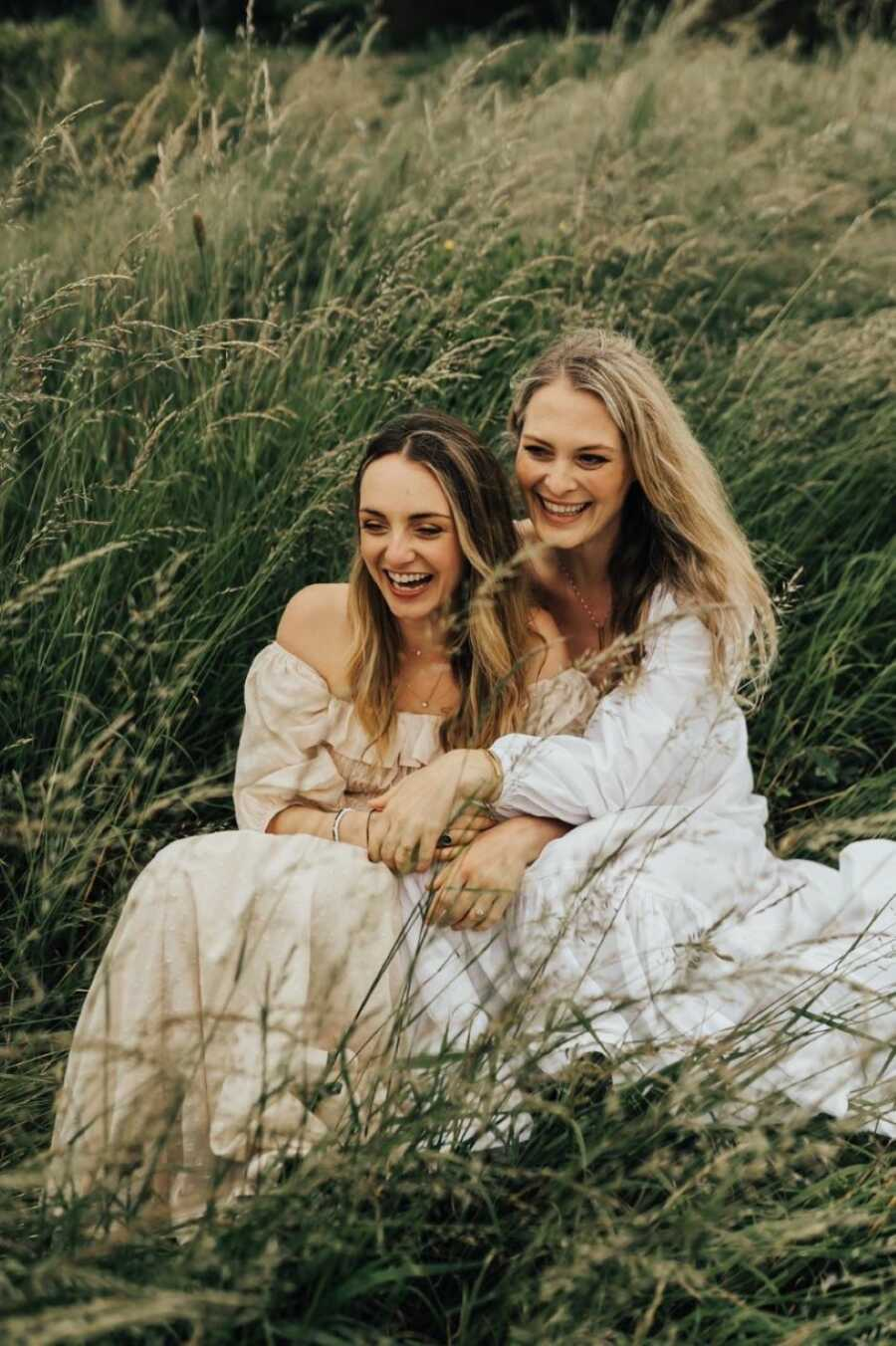 Two women engaged to be married wear long flowy dresses while taking photos in a field of wheat