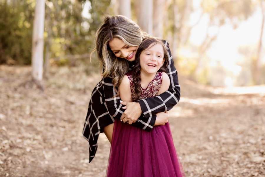 Young widowed mother hugs her only daughter during a fall photoshoot in the woods together