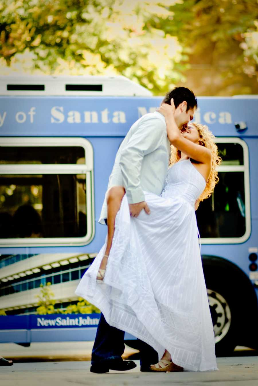 Young couple celebrate their love in intimate kiss during a photoshoot with a Santa Monica bus behind them