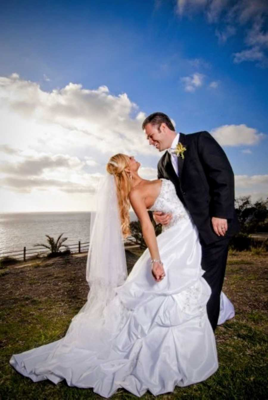 Newlywed couple take beautiful photo together overlooking a cliff at the Point Vicente Lighthouse in California