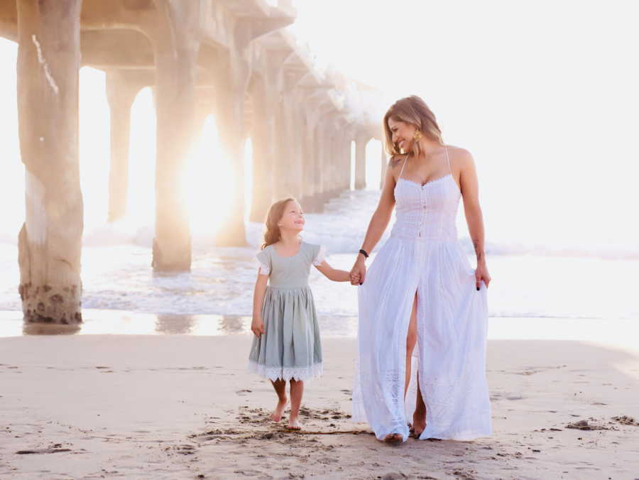 Young widow walks on the beach in a white dress with her daughter she fought so hard to have