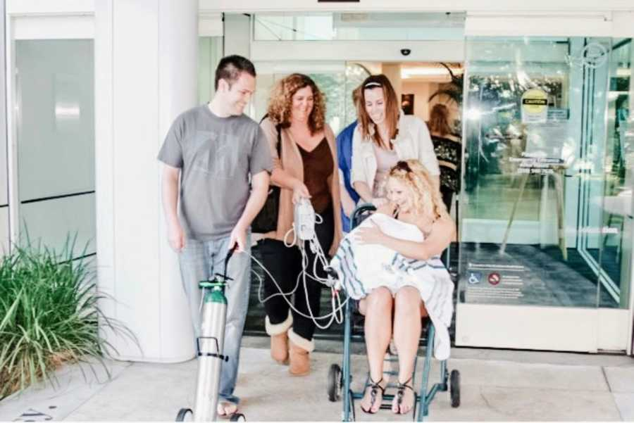 New mom gets wheeled out of the hospital with her newborn baby attached to an oxygen tank