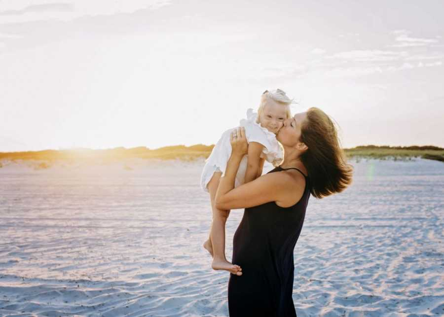 Mom of two kisses her daughter with Down syndrome while they take family photos on the beach at sunset