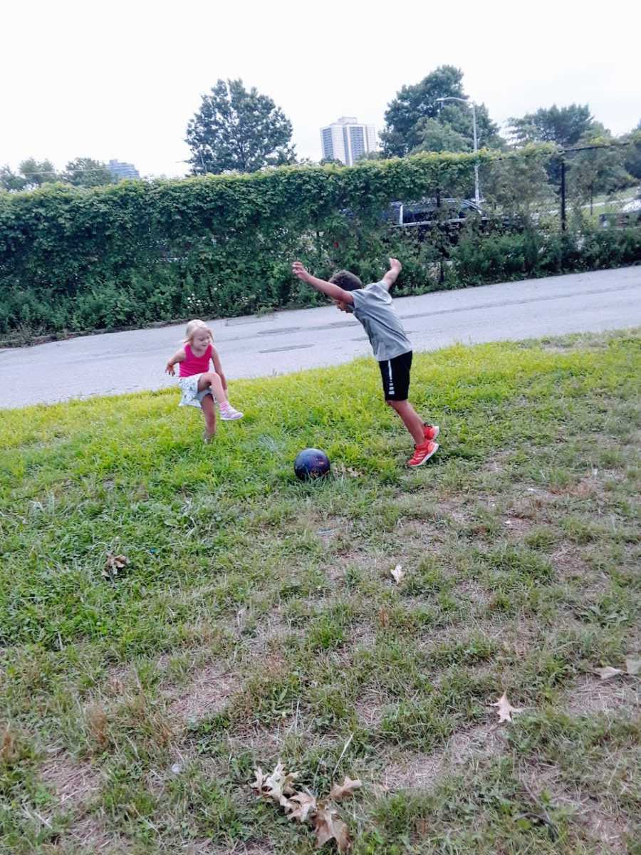 Siblings play with a soccer ball in their backyard during summer as their mom watches on