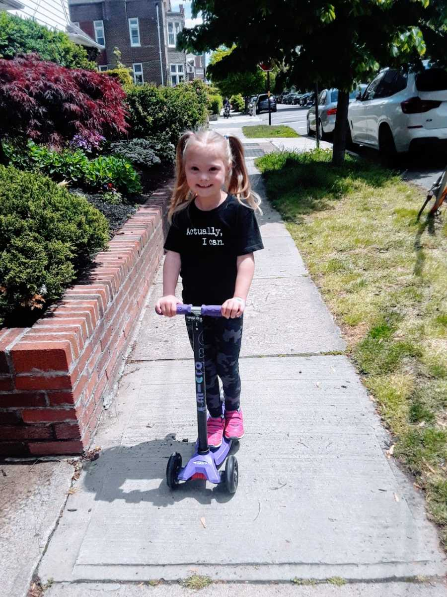"""Young girl with Down syndrome rides on a scooter while wearing a shirt that says """"Actually, I can."""""""