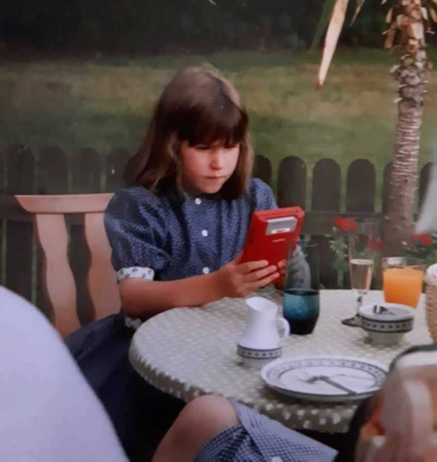 young girl sitting at a table on her phone