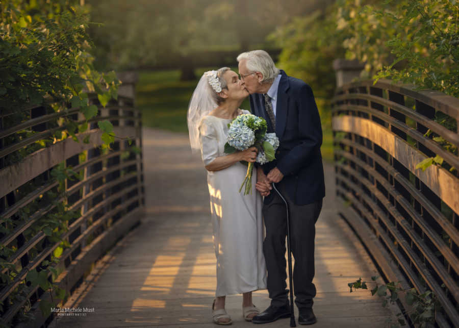 Couple celebrating their 50th wedding anniversary share a sweet kiss during a photoshoot celebrating their love